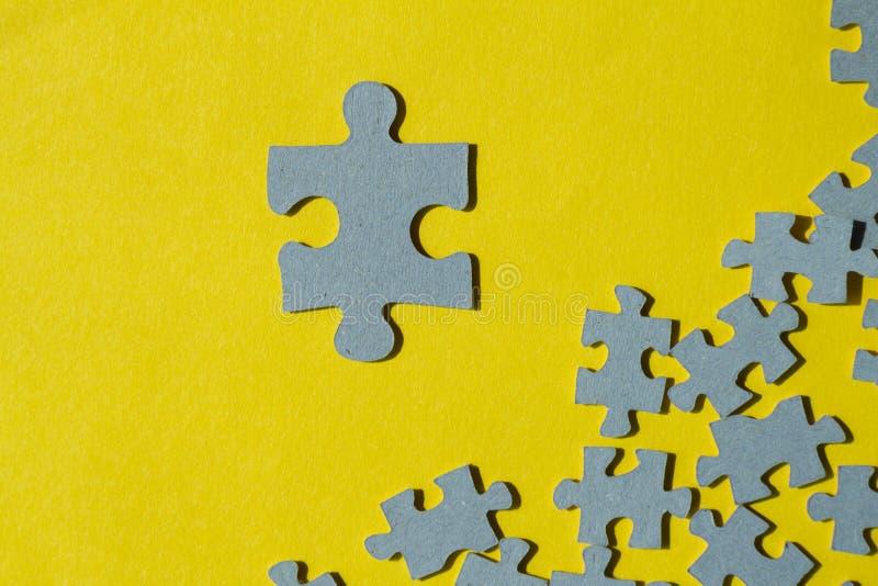 Un pezzo del puzzle contro il mucchio dei pezzi sul backgro giallo fotografia stock libera da diritti