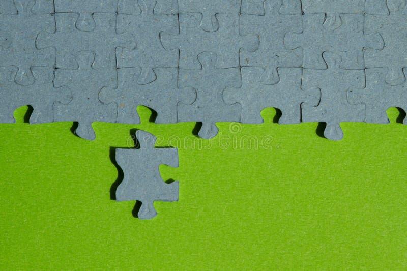 Un pezzo del puzzle tagliato su fondo verde immagine stock libera da diritti