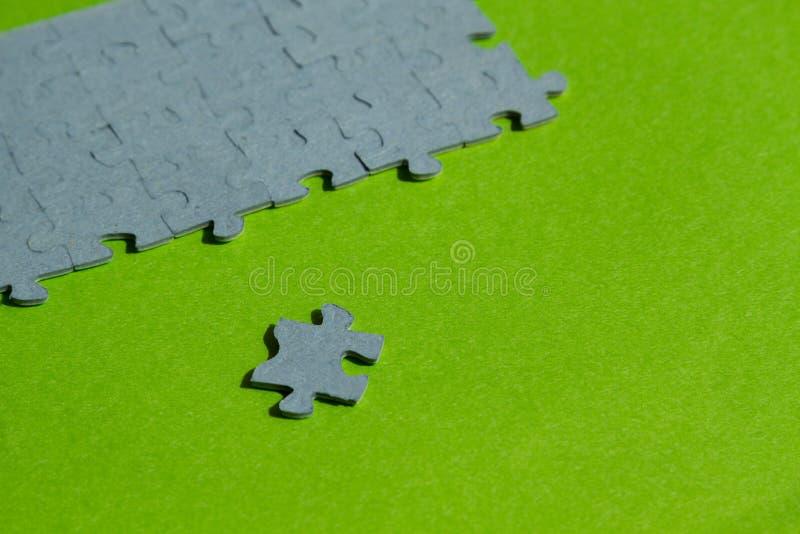Un pezzo del puzzle tagliato su fondo verde fotografia stock