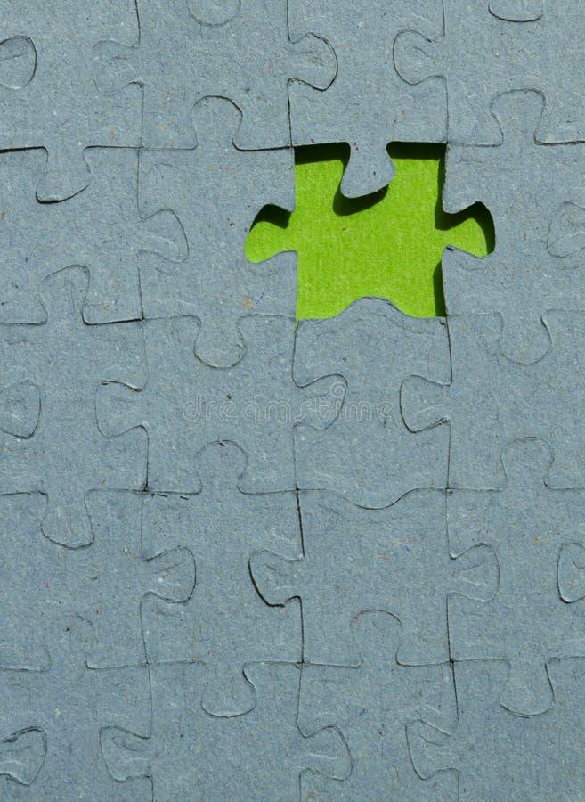 Un pezzo del puzzle tagliato su fondo verde fotografie stock libere da diritti