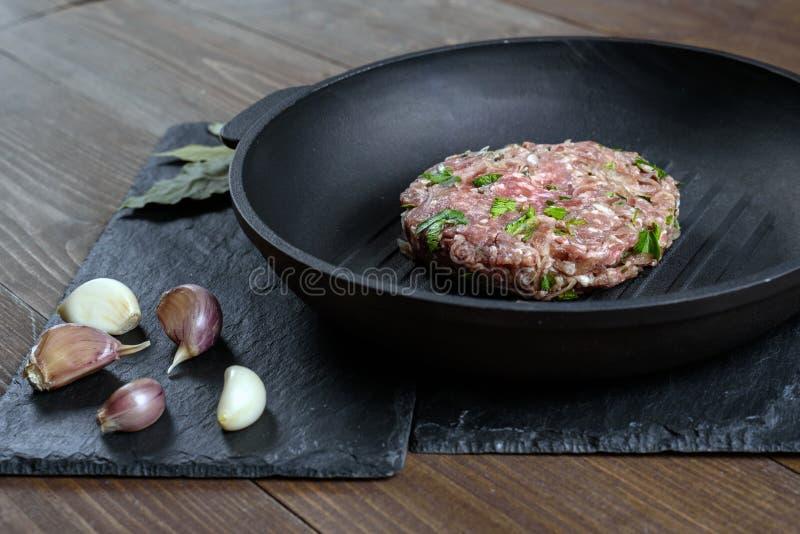 Un pezzo di carne tritata cruda con le erbe e di aglio su una leccarda del ghisa si trova su una pietra grigia immagini stock libere da diritti