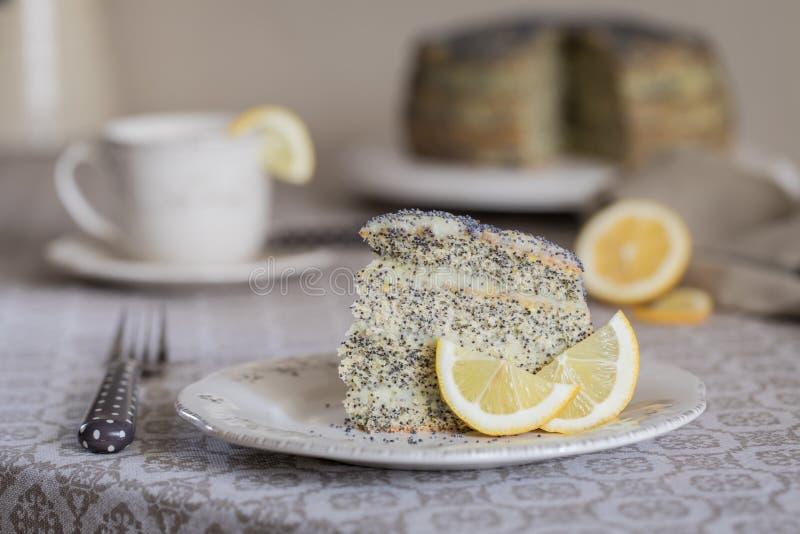 Un pezzo di dolce con i semi di papavero e crema del limone e una tazza di tè fotografia stock libera da diritti