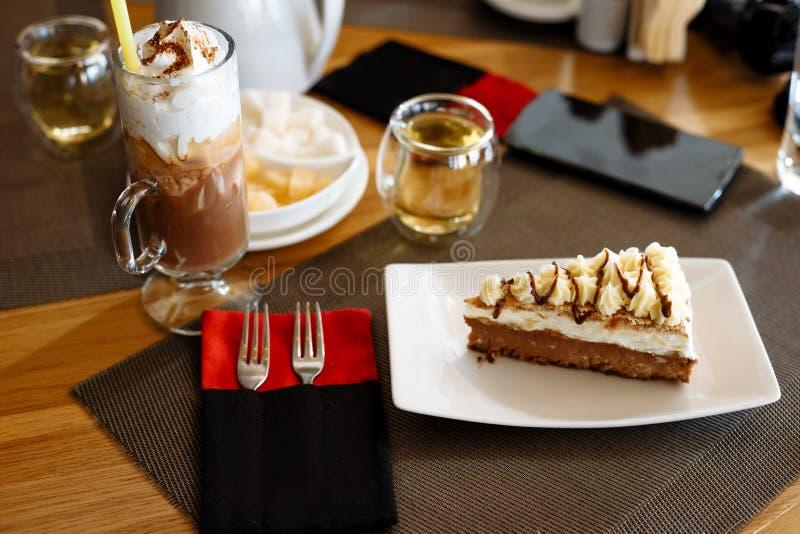 Un pezzo di dolce, di frapp? in un vetro, di teiera, di tazze di t? e di coltelleria su una tavola in un caff? fotografie stock libere da diritti