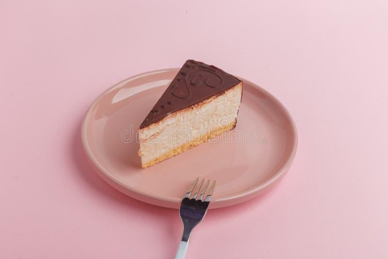 Un pezzo di dolce, torta di formaggio su un piatto con una forcella su un fondo rosa fotografie stock