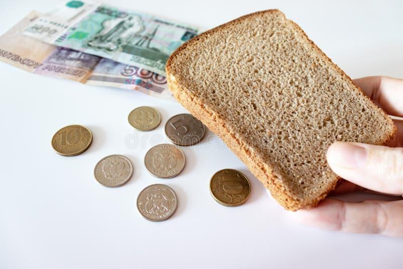 Un pezzo di pane nero a disposizione e monete e rubli di carta sulla tavola Il concetto di povertà, mancanza di fondi per aliment fotografia stock libera da diritti