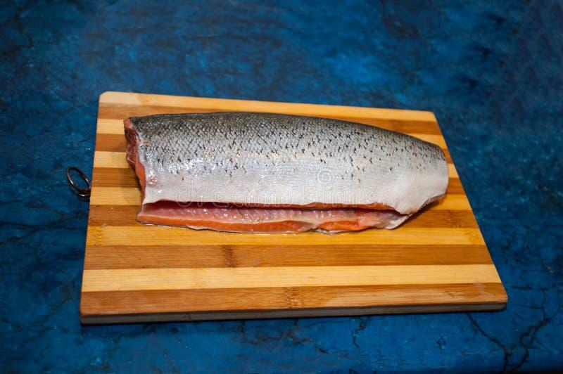 Un pezzo di pesce fresco, crudo, rosso su un tagliere marrone di legno, su un fondo nero Bello raccordo di color salmone che si t immagine stock