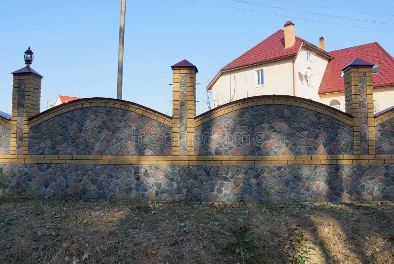 Un pezzo di recinto di pietra grigio fuori nell'erba fotografia stock libera da diritti