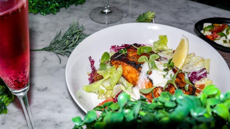 Un pezzo di salmone arrostito con il limone, il sale e le verdure - decorazione operata dell'alimento fotografia stock