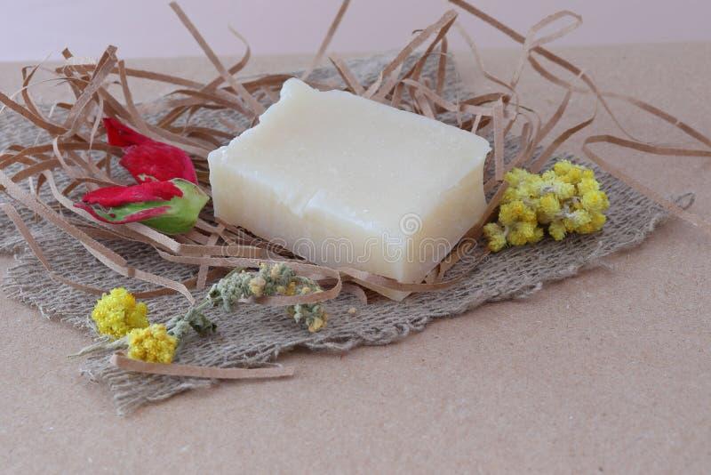 Un pezzo di sapone fatto a mano fragrante bianco su una palla delle strisce di carta su un tovagliolo del panno grezzo fotografia stock
