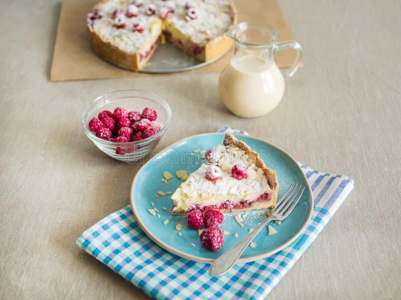 Un pezzo di torta di mascarpone con i raspberris ed il latte freschi fotografia stock