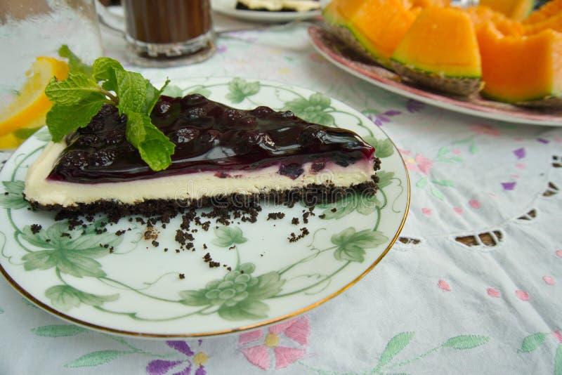 Un pezzo di torta di formaggio deliziosa del mirtillo di freschezza con una menta immagini stock