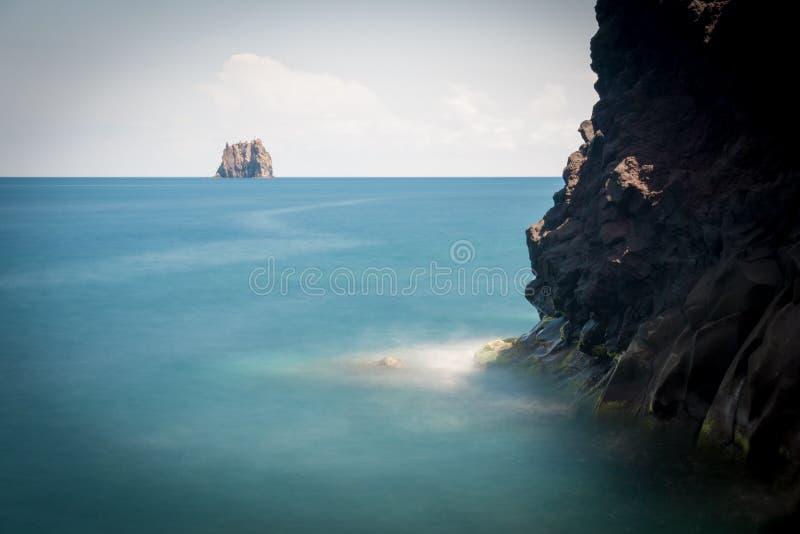 Un phare sur une petite île, vue d'une falaise avec la roche noire photo stock