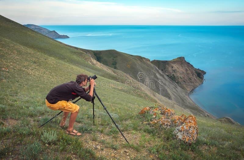 Un photographe avec un tr?pied et un appareil-photo fait des photos des paysages sur la montagne images libres de droits