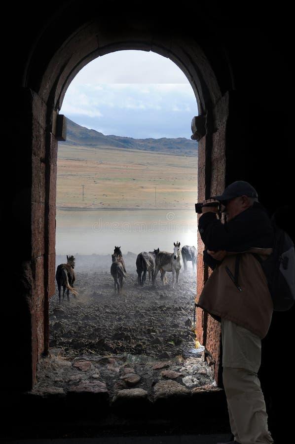 Un photographe de haut niveau derrière la fenêtre image stock