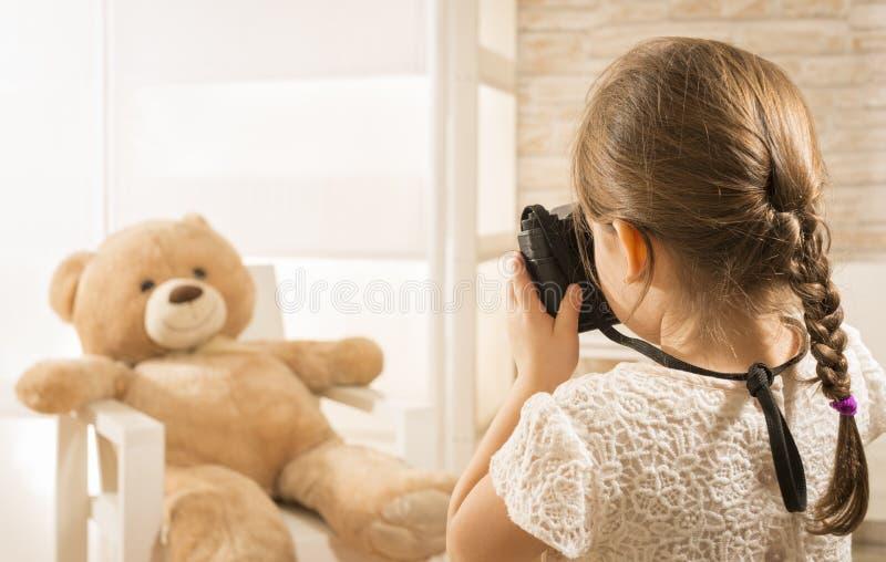 Un photographe de petit enfant prend une photo à son ours de nounours image libre de droits