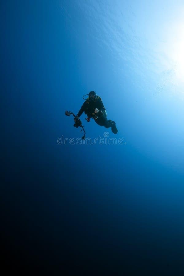 Un photographe sous-marin à l'extérieur dans l'océan bleu. images libres de droits