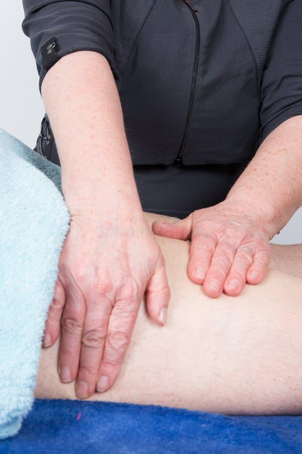 un physio- thérapeute de femme donnant le massage de genou d'homme photos libres de droits