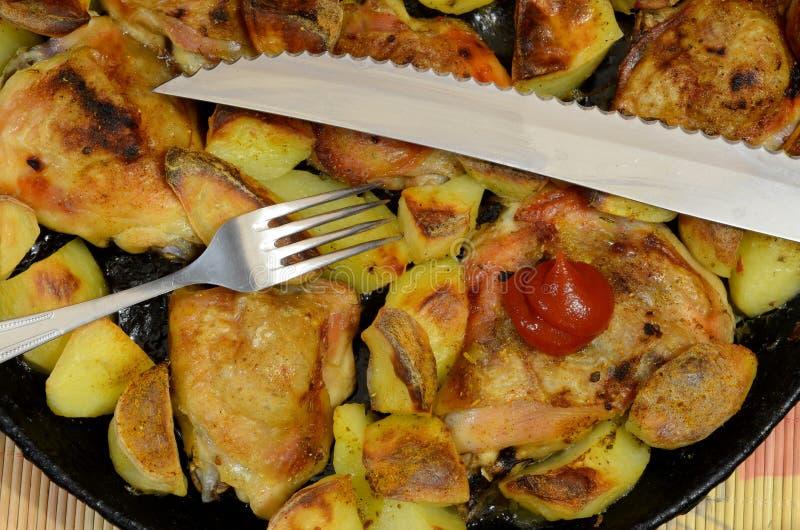 Un piatto che consiste delle patate fritte con le coscie di pollo e le spezie fotografia stock