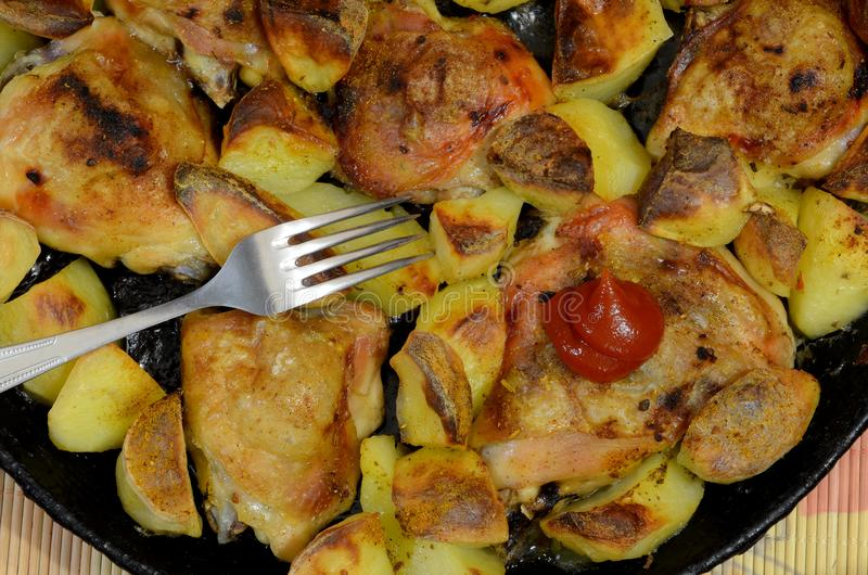 Un piatto che consiste delle patate fritte con le coscie di pollo e le spezie fotografia stock libera da diritti