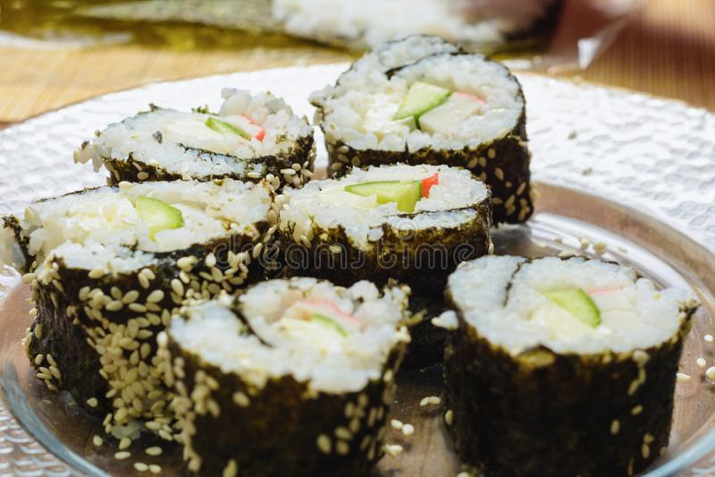 Un piatto con i ruoli dei sushi nella cucina, cucinata dal cuoco unico di una donna con le sue proprie mani fotografia stock libera da diritti