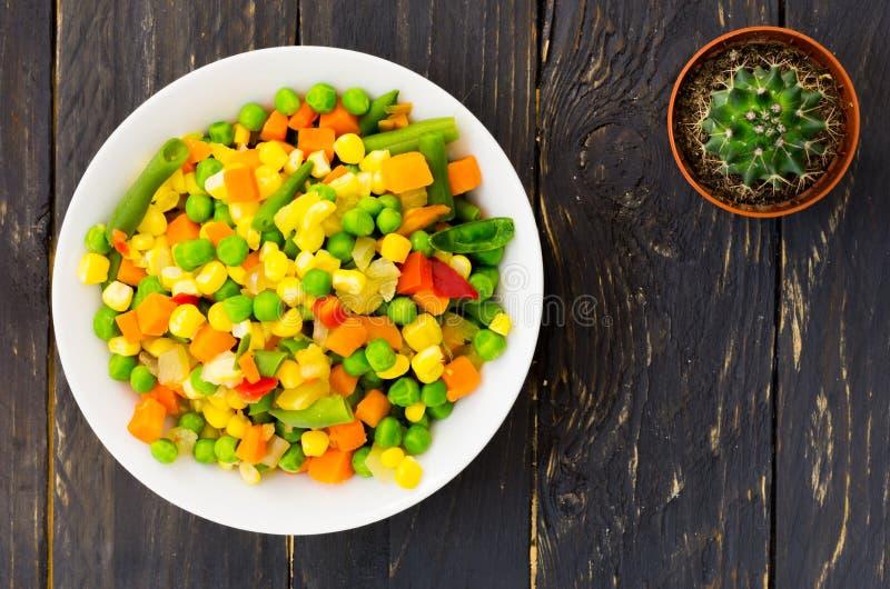 Un piatto con insalata messicana e un cactus su un fondo nero Un'insalata variopinta Vista superiore fotografie stock libere da diritti