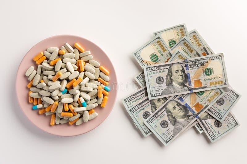 Un piatto con le pillole ed il mucchio dei dollari isolati su bianco immagini stock