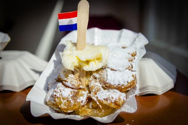 Un piatto con Poffertjes cotto fresco con la banana Poffertjes ? un ossequio olandese tradizionale della pastella fotografie stock libere da diritti