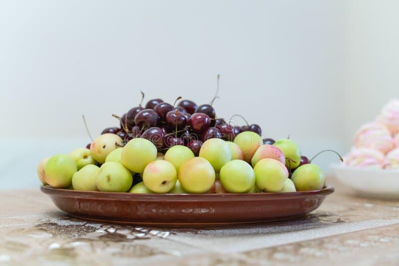 Un piatto con una frutta fresca e le bacche Ciliegie, albicocche, pesche e nettarine fotografie stock libere da diritti