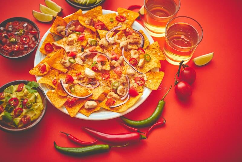 Un piatto dei nacho deliziosi della tortiglia con la salsa di formaggio fusa, pollo arrostito fotografie stock