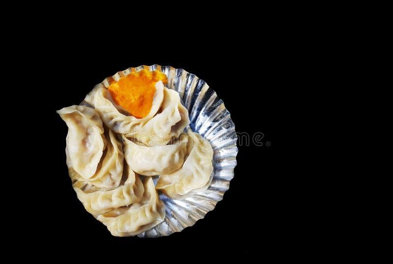 Un piatto del momo cotto a vapore veg con il chutney della salsa nel fondo nero fotografia stock