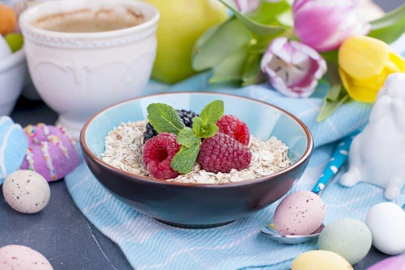Un piatto della farina d'avena con i lamponi e la menta freschi Caffè aromatizzato Un mazzo dei tulipani della molla immagini stock