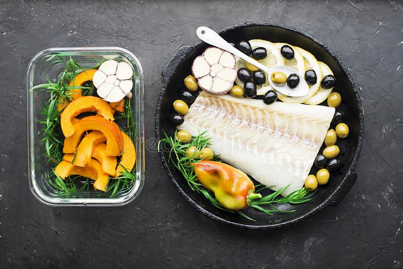 Un piatto di cucina sana con frutti di mare: il merluzzo è un pesce di mare bianco con le fette del limone, olive, sale marino ne immagini stock libere da diritti