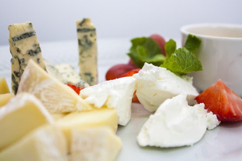 Un piatto di parecchi generi di formaggi in assortimento, con le fragole e l'uva immagine stock libera da diritti