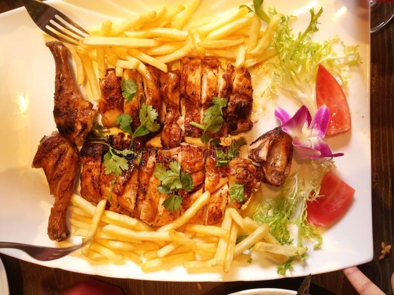 Un piatto di pollo arrosto e delle patatine fritte, delizioso fotografia stock