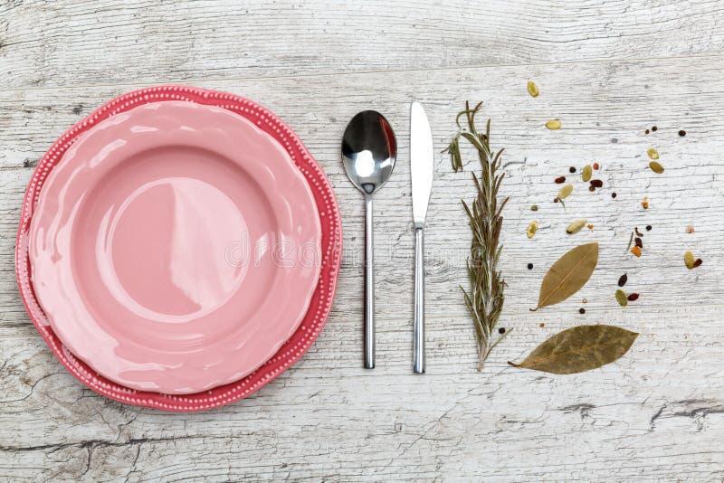 Un piatto rosa con un cucchiaio e un coltello su una tavola grigia fotografia stock libera da diritti