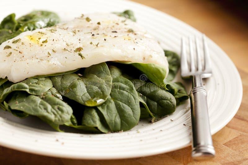 Un piatto semplice di spinaci organici per pranzo con i piatti delle erbe e sale rosa più Olive Oil immagini stock