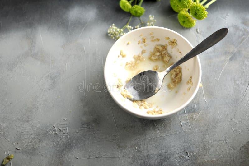 Un piatto sporco con il resti di alimento su un fondo grigio e su uno spazio libero per testo Vista superiore fotografie stock