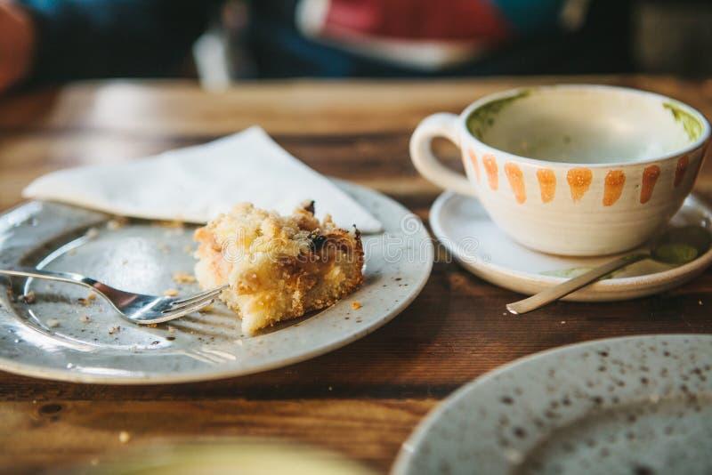 Un piatto sporco e una tazza di caffè vuota Il bigné mangiato per metà su un piatto Piatti vuoti dopo il cibo su una tavola di le fotografia stock