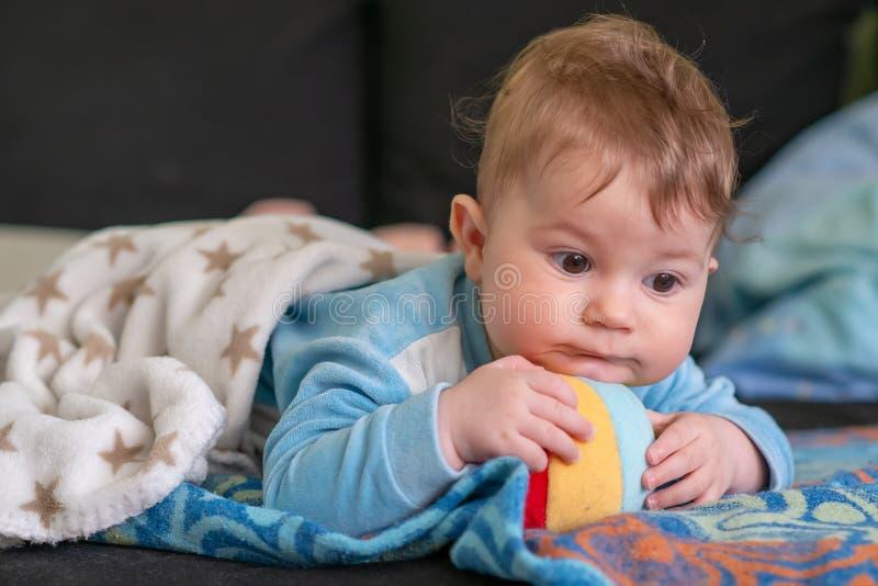 Un piccolo bambino adorabile che si trova sul suoi stomaco e giochi con della la palla molle colorata multi fotografie stock