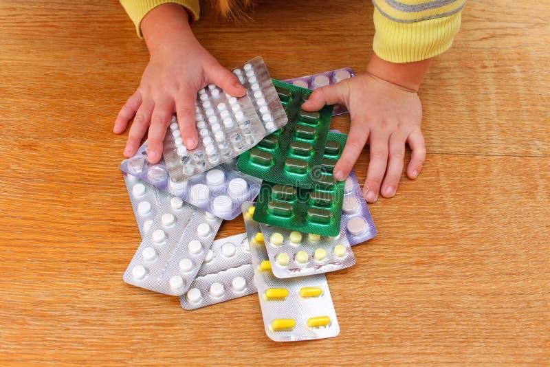Un piccolo bambino che gioca con le medicine immagini stock libere da diritti