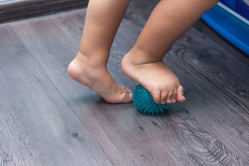 Un piccolo bambino che massaggia i suoi piedi mentre stando sulla palla di massaggio immagini stock libere da diritti