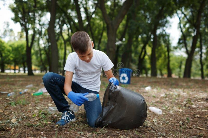 Un piccolo bambino che prende l'immondizia e che la mette in una borsa di immondizia nera su uno sfondo naturale Protezione di ec fotografia stock
