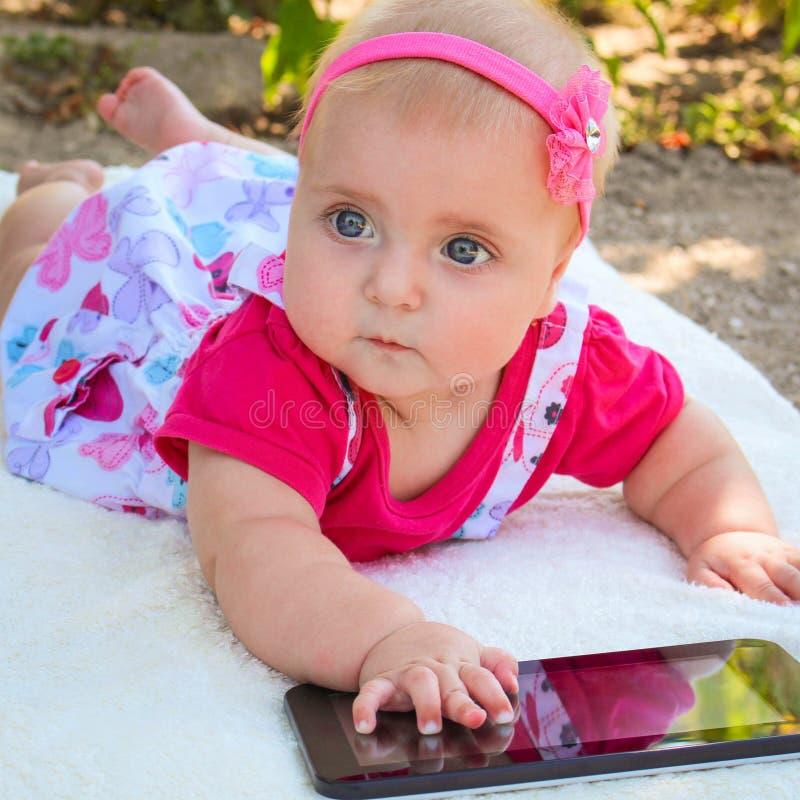 Un piccolo bambino che si trova sul suo stomaco, giocante con una compressa immagine stock libera da diritti