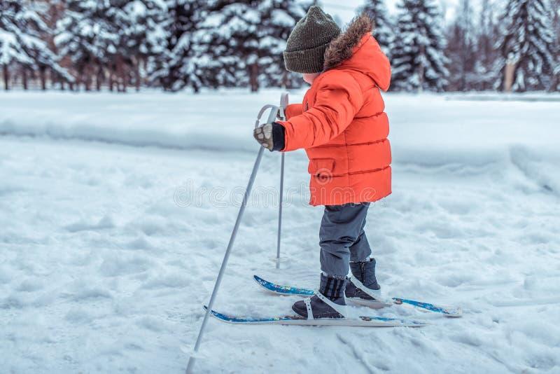 Un piccolo bambino di 3-5 anni, un ragazzo nell'inverno sugli sci dei bambini, in un rivestimento ed in un cappello caldi I giri  fotografie stock