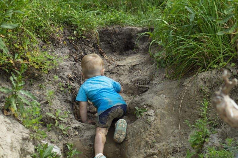 Un piccolo bambino fa uno sforzo per scalare la montagna immagini stock