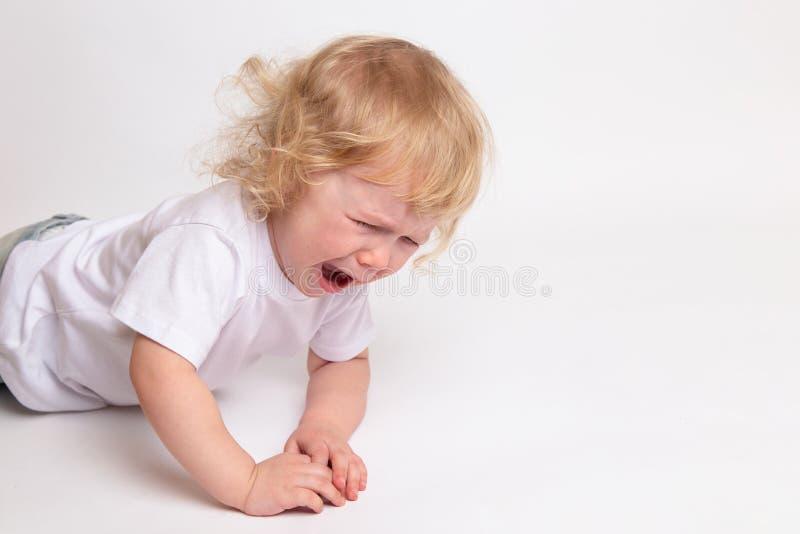 Un piccolo bambino gridante riccio in una maglietta bianca pulita sta trovandosi sul pavimento e sul gridare fotografie stock libere da diritti