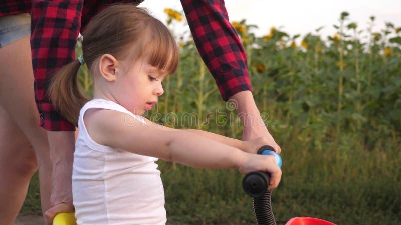 Un piccolo bambino impara guidare una bici La mamma insegna alla figlia a guidare una bici Giochi della madre con la sua piccola  fotografia stock