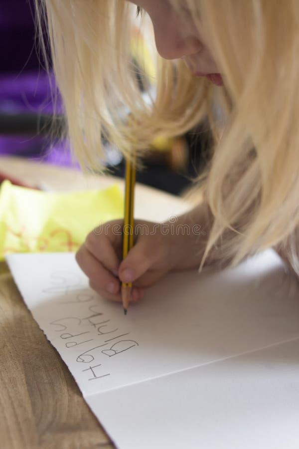 Un piccolo bambino scrive un biglietto di auguri per il compleanno alla sua zietta immagini stock