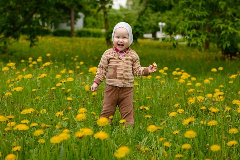 Un piccolo bambino sta nelle risate del prato fotografia stock