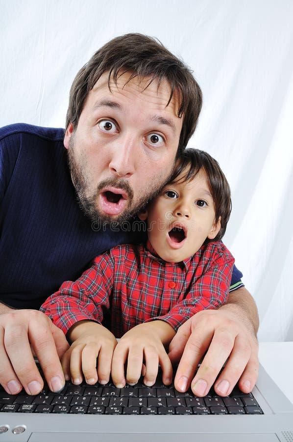 Un piccolo bambino sveglio con un computer portatile scosso immagine stock libera da diritti